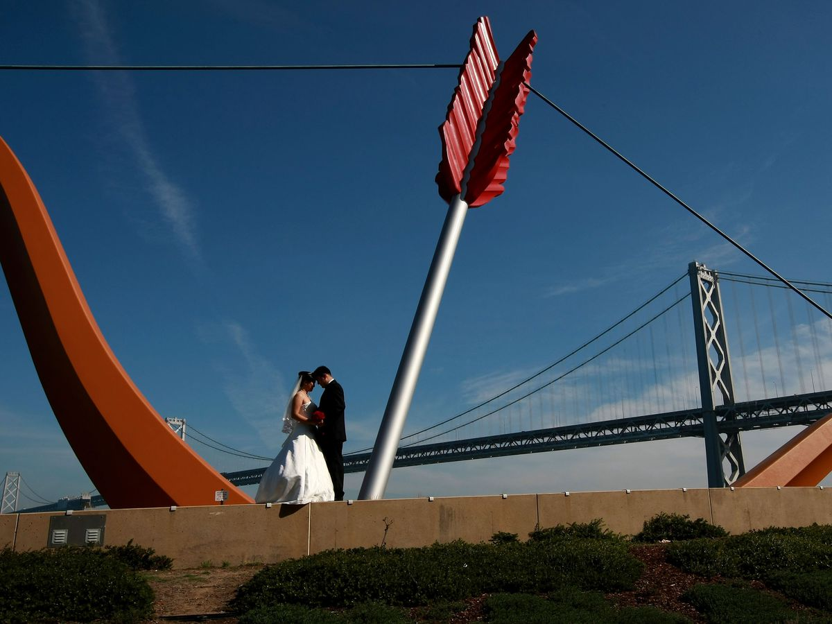 Two people stand next to a large sculpture of a bow and arrow called Cupid's Span in San Francisco. In the background is a bridge spanning across a body of water.
