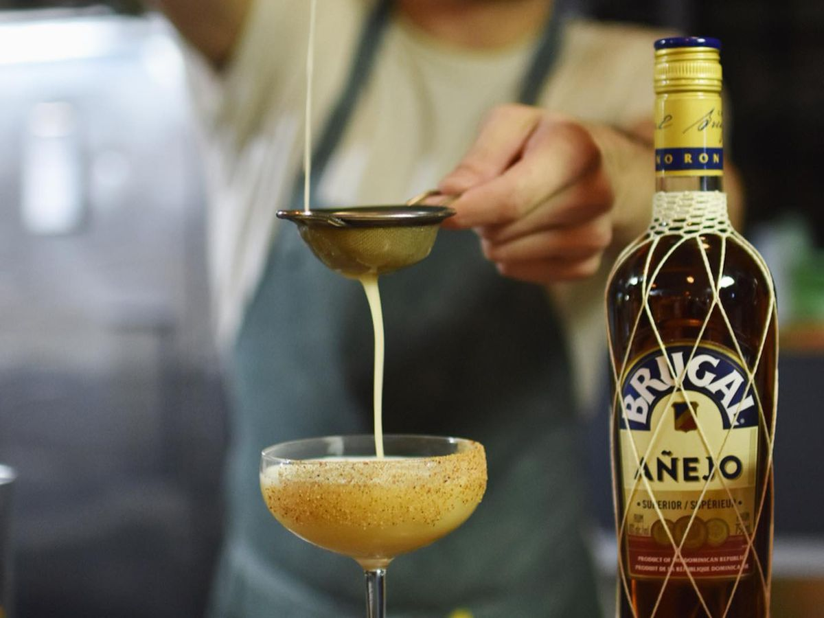 A bartender pours a cocktail through a strainer into a coupe.