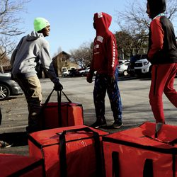 Mountain View Elementary student Ali Bwana, left, and Glendale Middle School students Dede Gass, Hassan Mutambala and Ali Hassan lift bags of lunches that they helped deliver to residents of Seasons at Pebble Creek in Salt Lake City on Tuesday, Dec. 29, 2020. Publik Kitchen cooked almost 300 meals over three days for Glendale Middle School students and their families through the Nourish to Flourish initiative. The initiative, which started in response to the COVID-19 pandemic, is a partnership between restaurants, service organizations and community funders to provide meals to those in need.