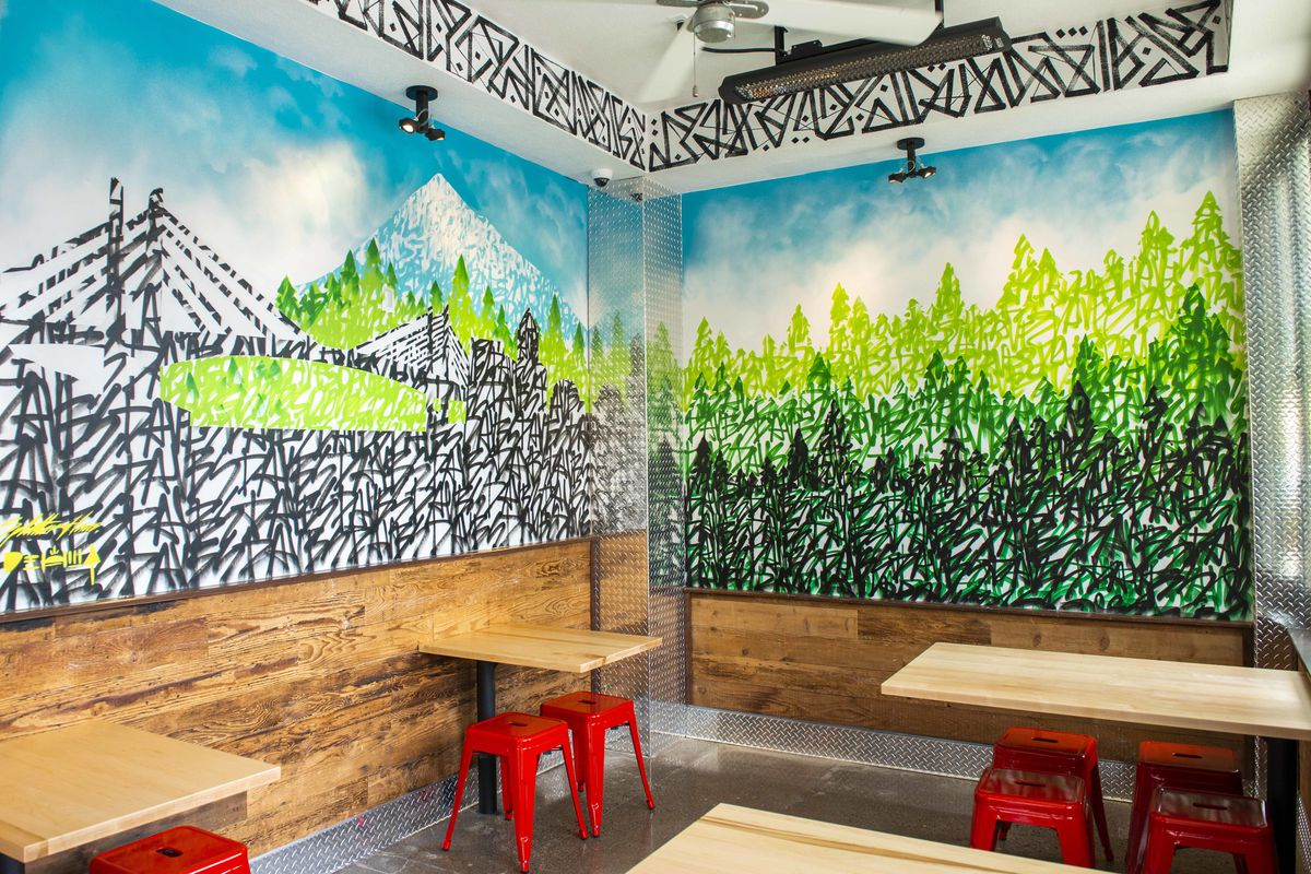 The corner of Dave's Hot Chicken has one panel of black and white scribbles that make up an illustration of a bridge, with Mt. Hood lurking in the background. On the other side, the wall is made up of three layers of illustrated trees.