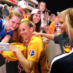 Utah Royals FC forward Amy Rodriguez (8) take photos with fans as her son Ryan reaches for her after a match against the Orlando Pride at Rio Tinto Stadium in Sandy on Wednesday, May 9, 2018.
