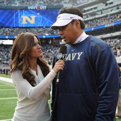 Navy head football coach Ken Niumatalolo is interviewed by a CBS reporter after a game.