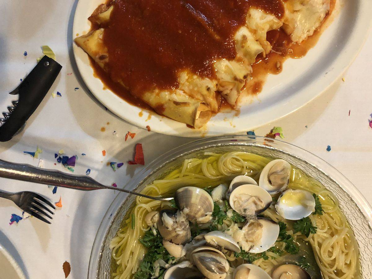 Baked manicotti and linguine with clam sauce on a table