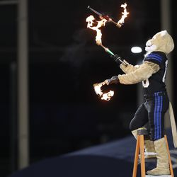 """BYU mascot """"Cosmo"""" juggles fire sticks in the first half of an NCAA college football game against San Diego State and BYU Saturday, Dec. 12, 2020, in Provo, Utah."""