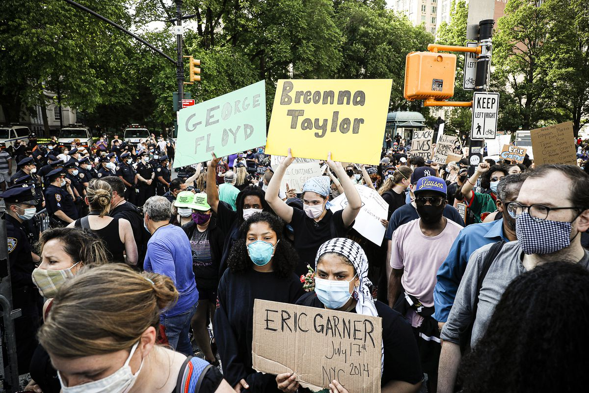 "A large, masked crowd fills a street. Three people hold signs, each with a name: ""George Floyd, Breonna Taylor, and Eric Garner."""