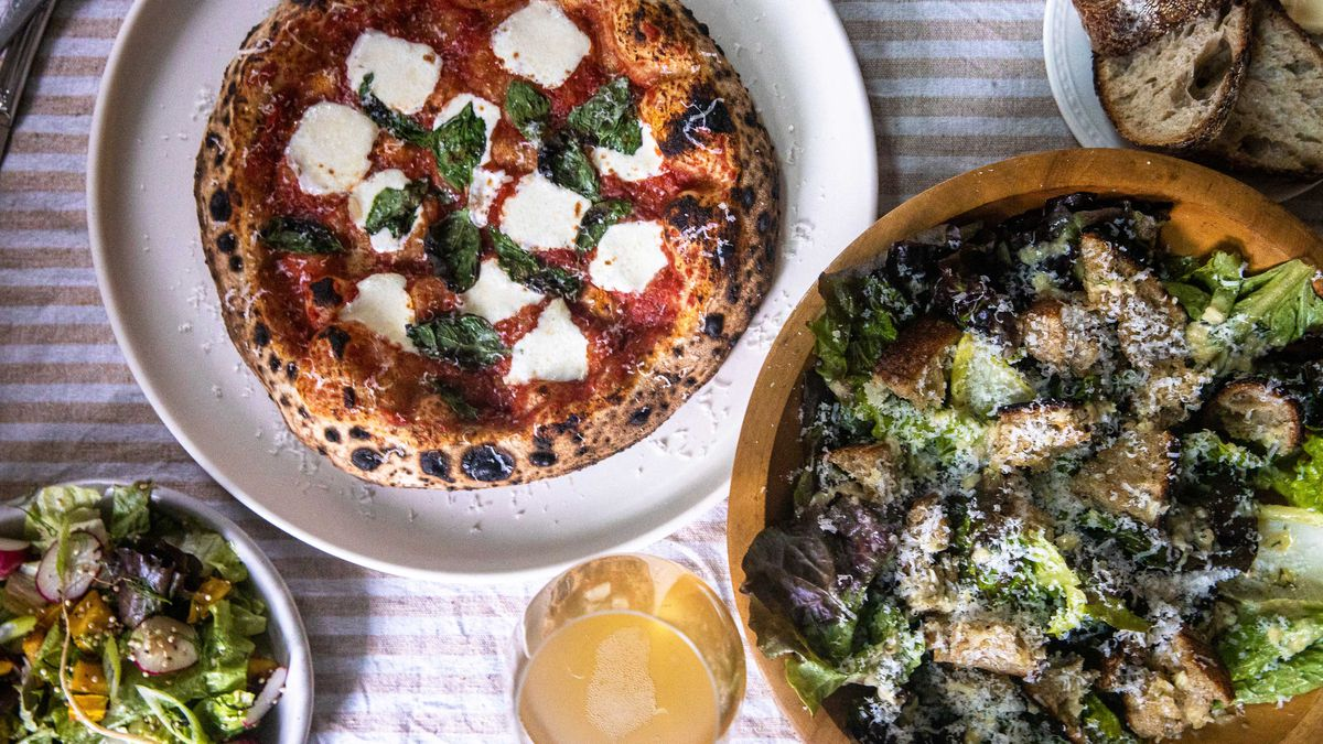 neapolitan style pizza and bowls of salad