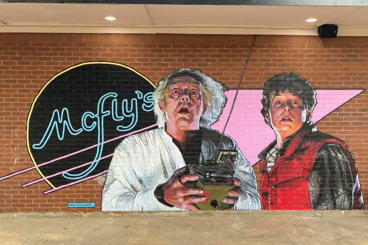 a mural of Marty Mcfly and Doc Brown, characters from the film Back to the Future. the mural is painted on a brick wall