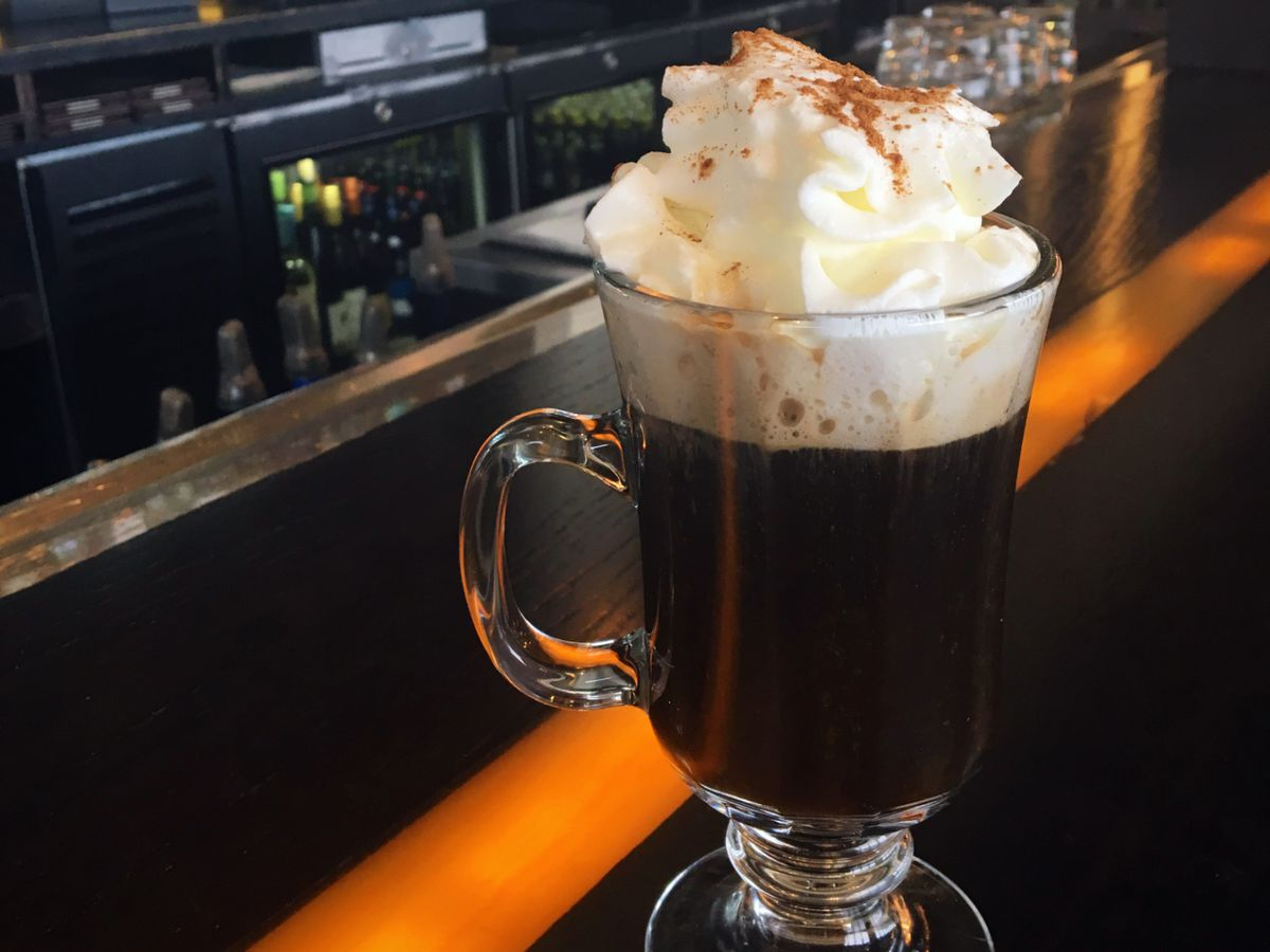 A Mexican coffee cocktail sits on a bar in a tall clear glass mug, garnished with whipped cream and ground cinnamon.