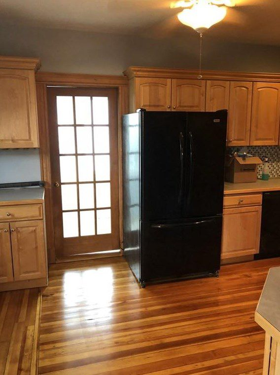 A largely empty kitchen with a fridge.