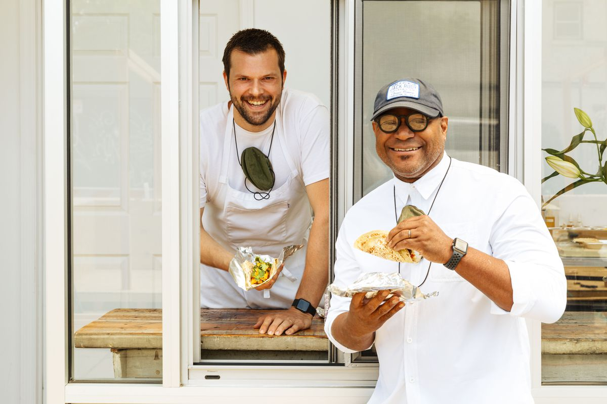 Two people smiling and holding tacos at a white-framed takeout window