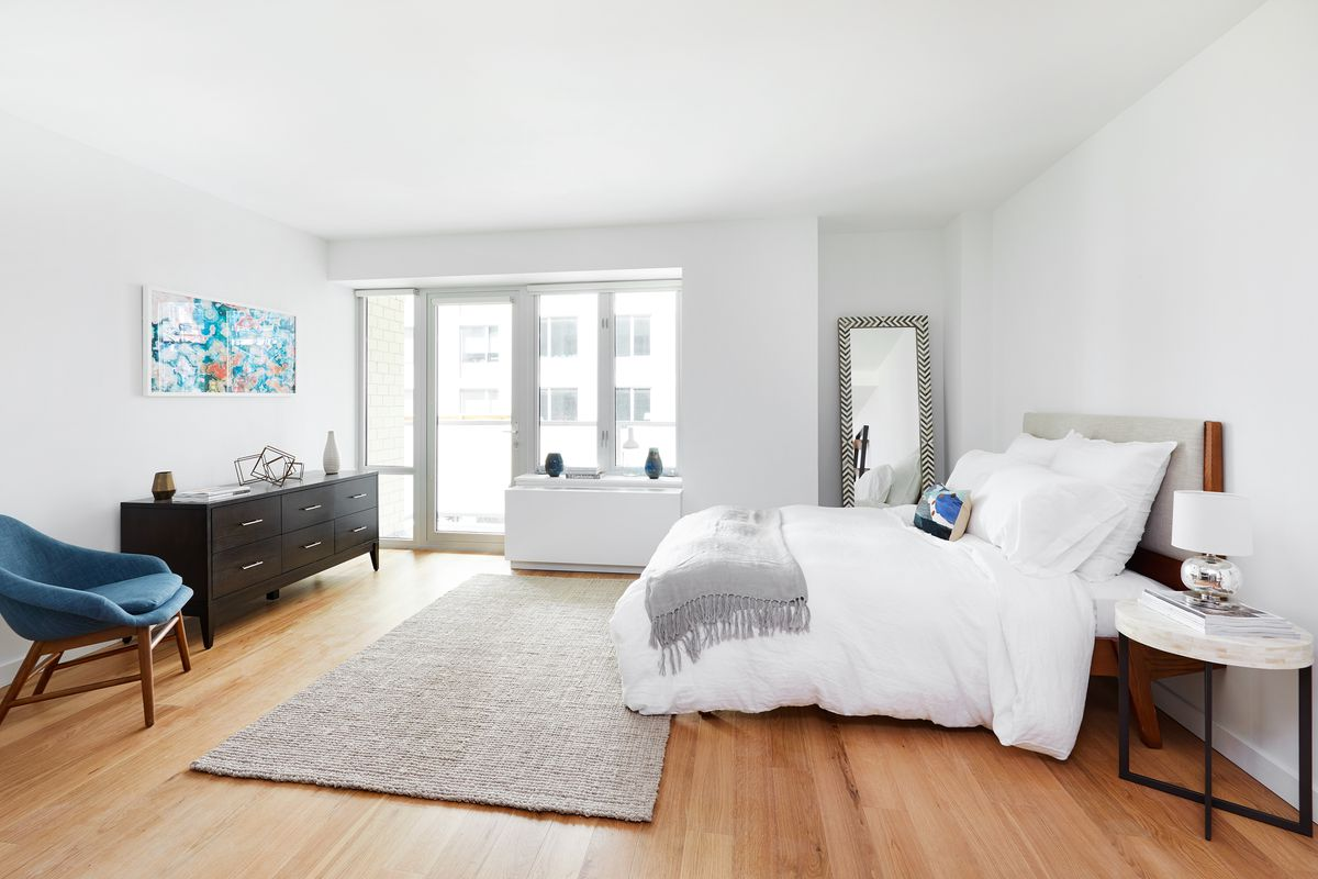 A bedroom with a large bed, hardwood floors, a large window, and white walls.