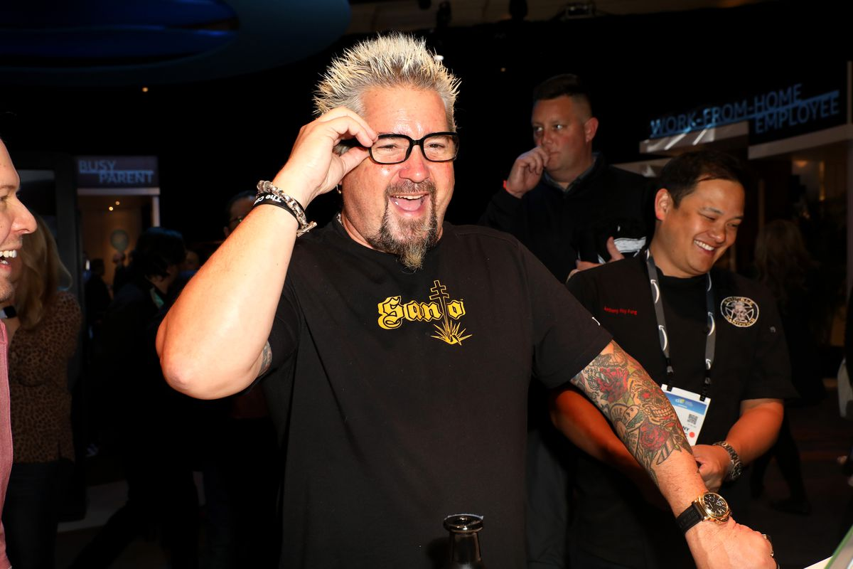 Guy Fieri, wearing a black t-shirt and glasses, walks by with his famously spiky blond hair