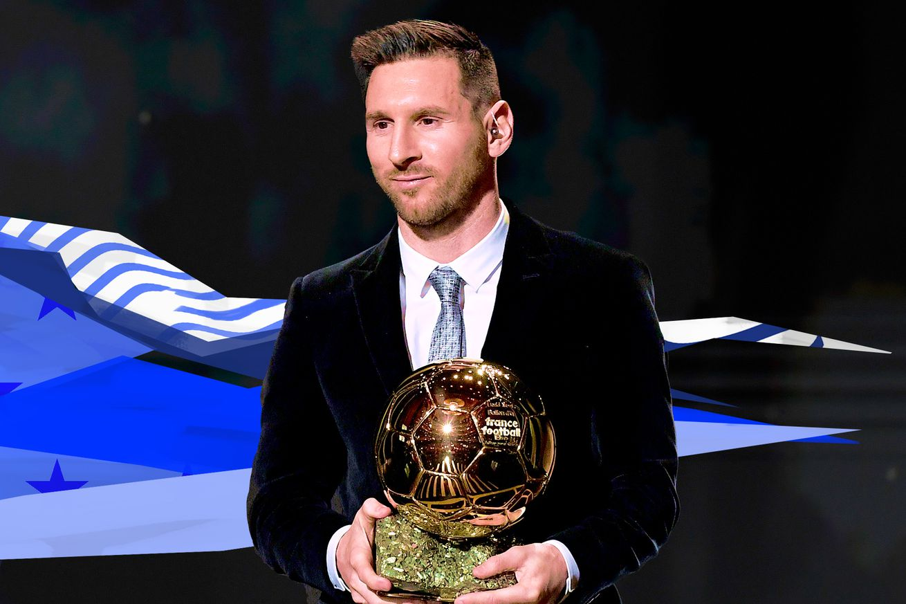 Photo of Lionel Messi in a suit holding the 2019 Ballon d'Or trophy.