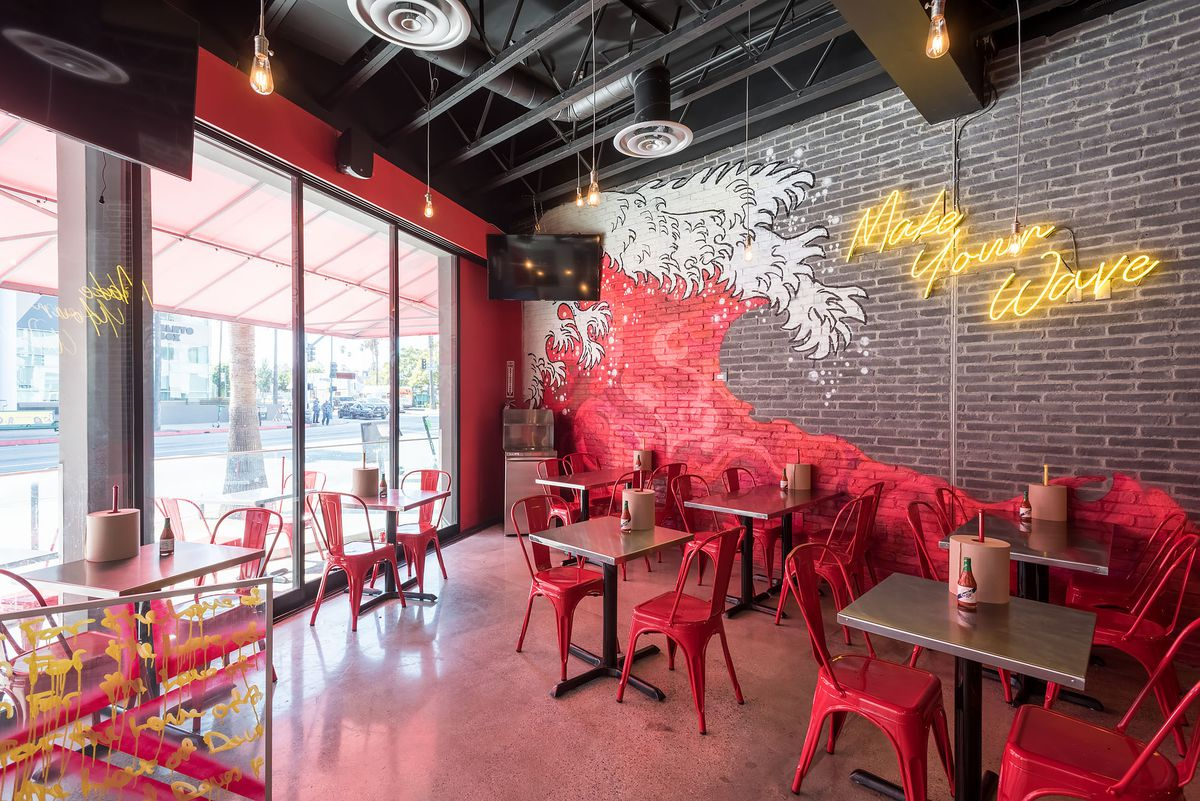 A red wave art and neon signage inside a restaurant.