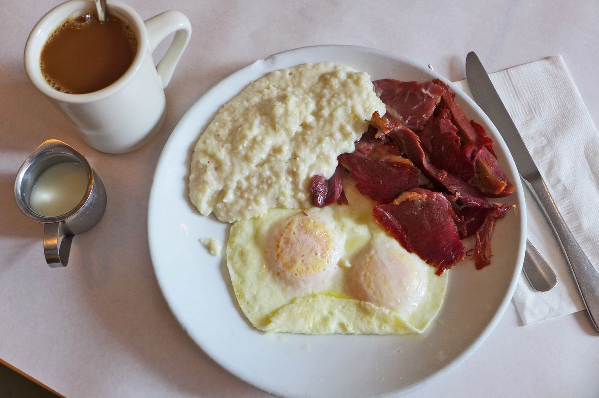 Two sunnyside up eggs at the bottom of the plate with grits on upper left and wadded ham on upper right.