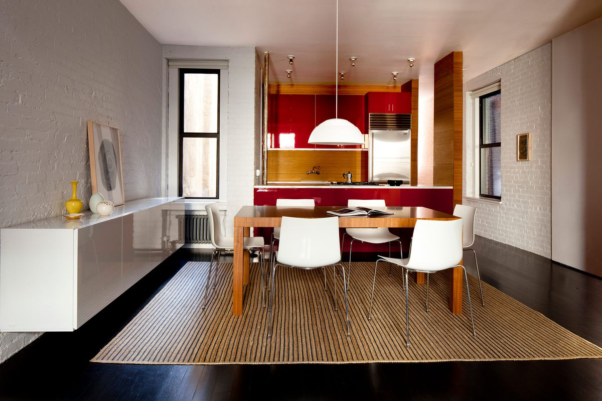 A view of the dining table with a red kitchen in the back.
