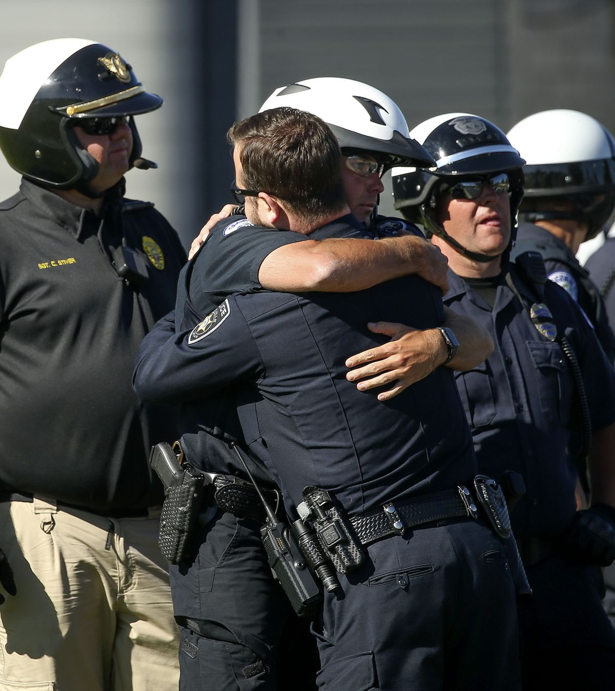 A Taylorsville and an Ogden law enforcement officer embrace after escorting the body of a fallen Ogden police officer to the Utah Medical Examiner's Office in Taylorsville on Thursday, May 28, 2020. Police said one officer and a suspect were killed, while another officer was injured, in an exchange of gunfire earlier in the day.