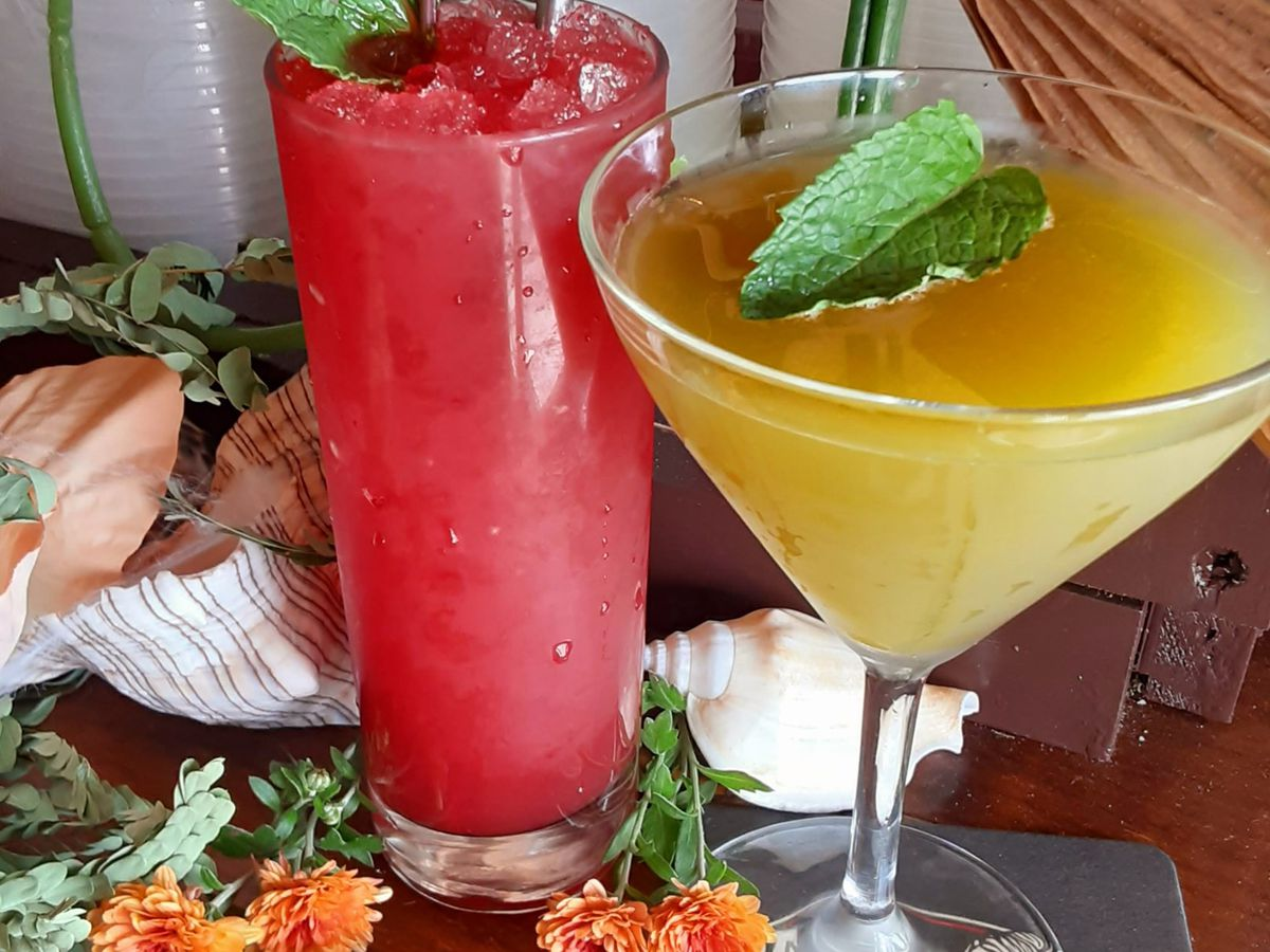 A red tall drink and an orange drink in a martini class on a bar with fresh flowers on it