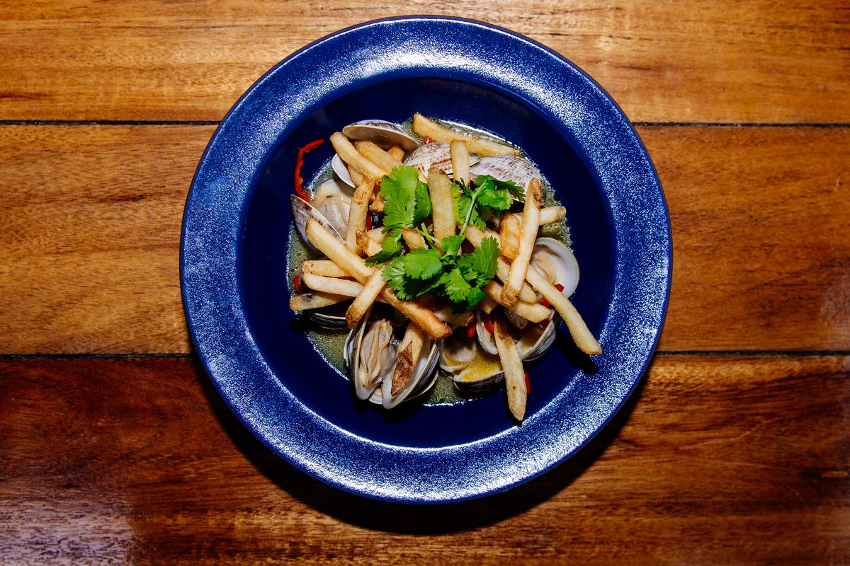 Overhead view of a blue bowl on a wooden table. The bowl is full of clams and fries.