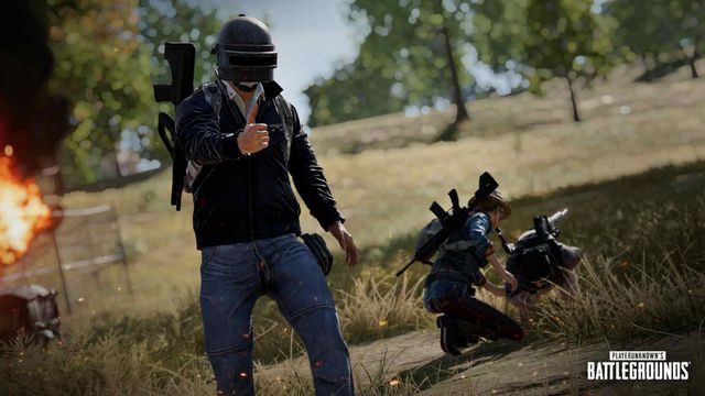 a player in PUBG's signature welder helmet raises their weapon while a teammate tends to a downed comrade