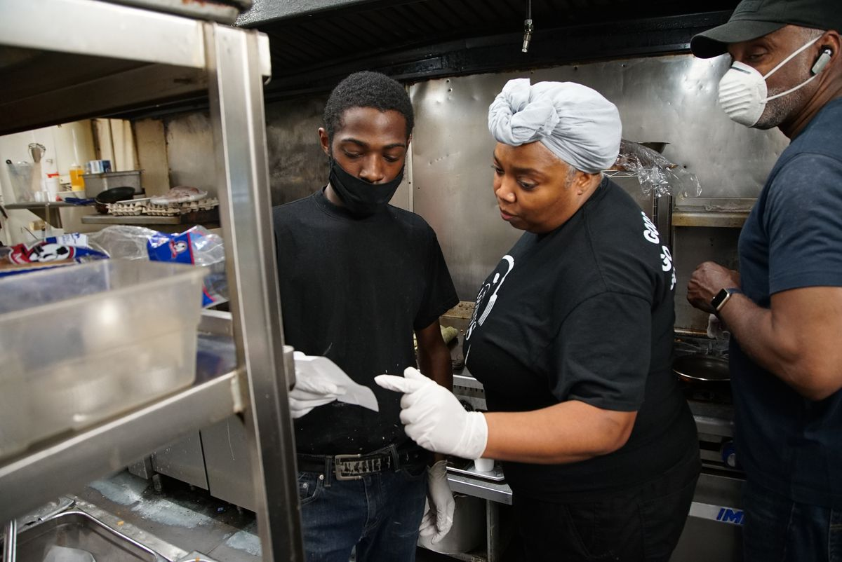 Constance Simms-Kincaid goes over takeout orders with employees at 5 Loaves Eatery on Friday, May 22, 2020.