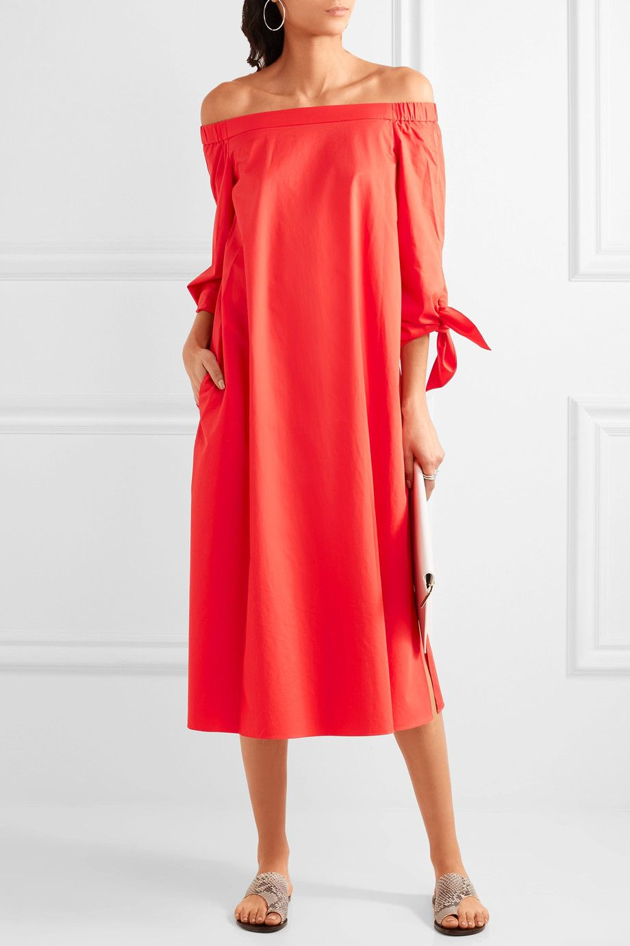 A model wearing a red off the shoulder dress
