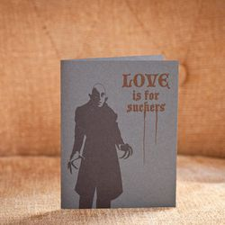 """<a href=""""http://blackheartletterpress.com/product/love-is-for-suckers/"""">Love is for Suckers Card</a>, $5 at Black Heart Letterpress"""