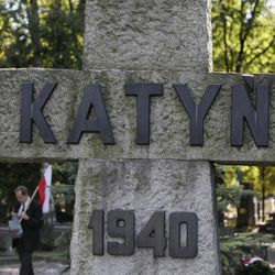 A man walks with a Polish flag near a memorial to the victims of Katyn, the Soviet massacre of 22,000 Polish officers in 1940, in Warsaw, Poland on Monday, Sept. 10, 2012. On Monday the U.S. National Archives is releasing about 1,000 newly declassified documents related to Katyn. Some shed further light on decades of suppression of Soviet guilt within the U.S. government. The cover-up began during World War II when the U.S. needed the Soviets to defeat Germany and Japan, and continued on some level long after.