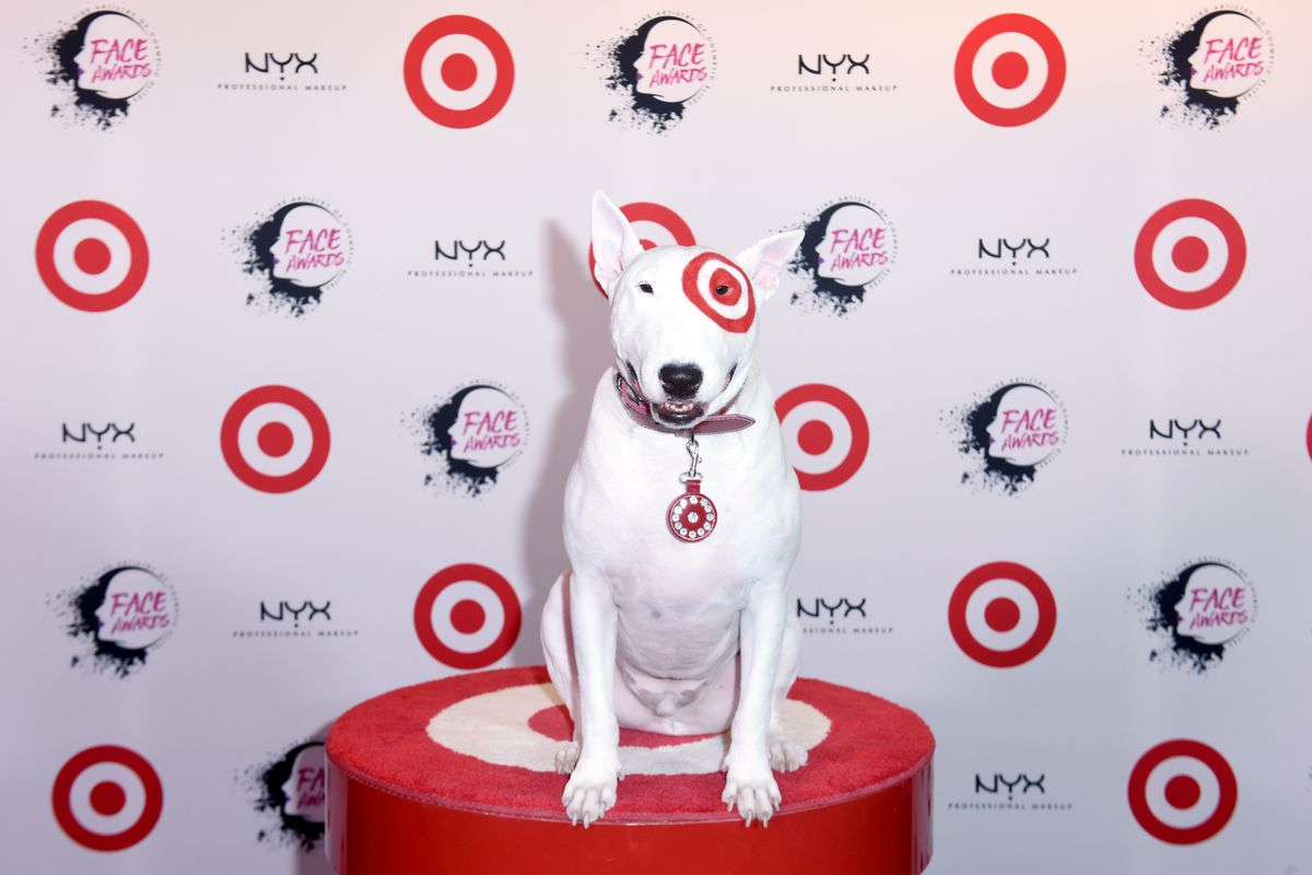 Target's dog, Bullseye, sits on a red Target-logo stool in front of a Target-themed backdrop.