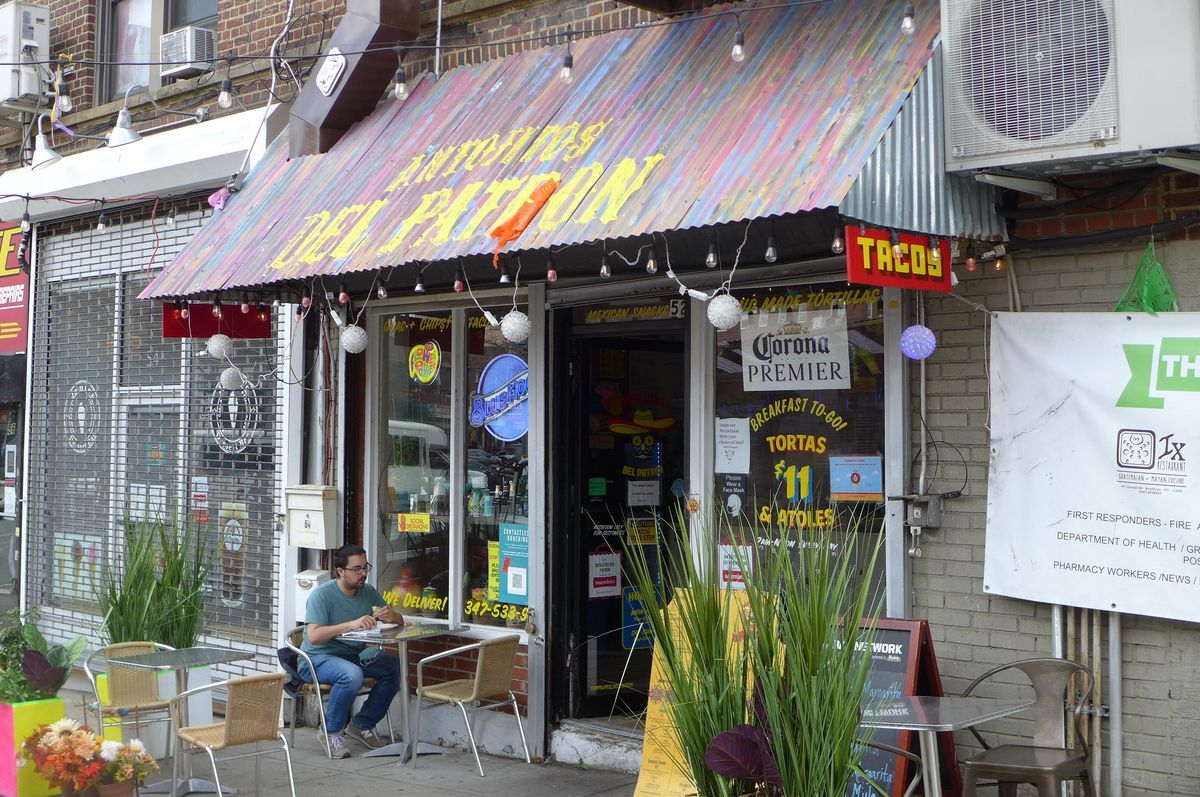 A small storefront with plants and tables out front and a corrugated aluminum overhang.