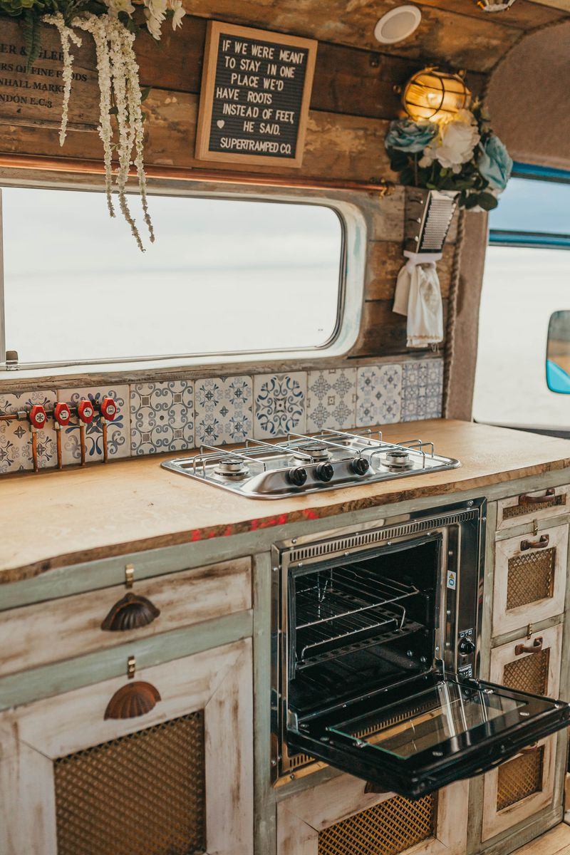 A close up of the camper's stove top, oven, and whitewashed cabinets. A large window and fake flowers sit above the stove top.