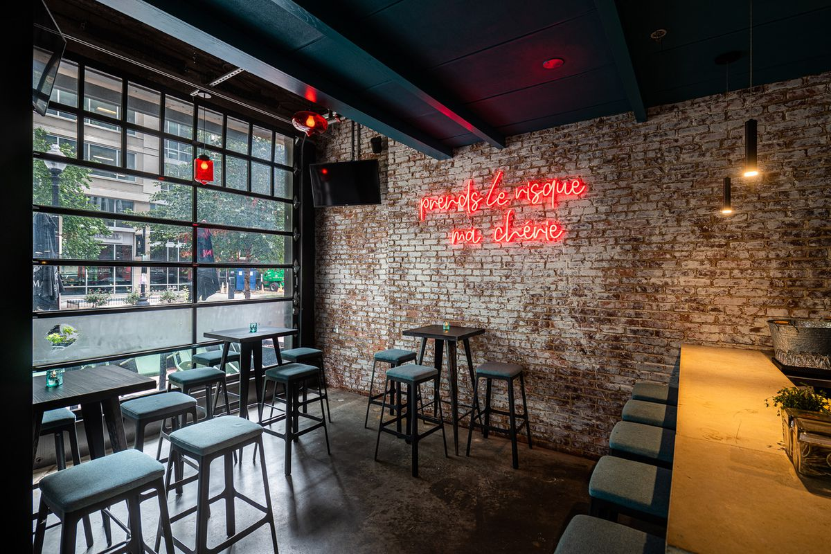 The main room at Bar Chinois features exposed brick, neon signs, and red light fixtures