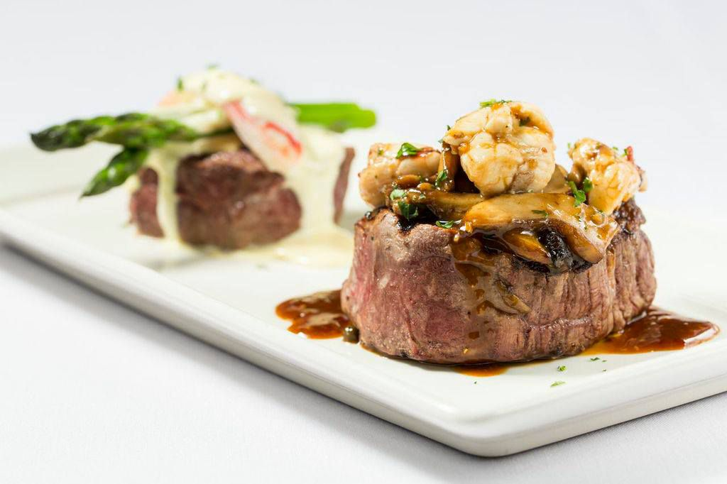 Two cuts of steak, one topped with shrimp and fixings, and the other with asparagus and sauce