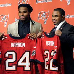 New Tampa Bay Buccaneers safety Mark Barron, left, and running back Doug Martin hold up their NFL football jerseys, Friday, April 27, 2012, during a news conference introducing them to the media in Tampa Bay, Fla. The Buccaneers selected Barron, the All-American who helped Alabama win two national titles with the seventh pick was the of the NFL draft on Thursday. Then in a surprise move, the team completed a trade that netted a second first-round pick and used it on Martin, of Boise State.