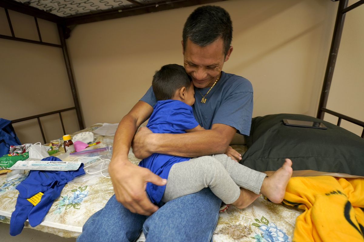 Elmer Maldonado, top, a migrant from Honduras, hugs his 1-year-old son at a shelter, Monday, March 22, 2021, in Harlingen, Texas.