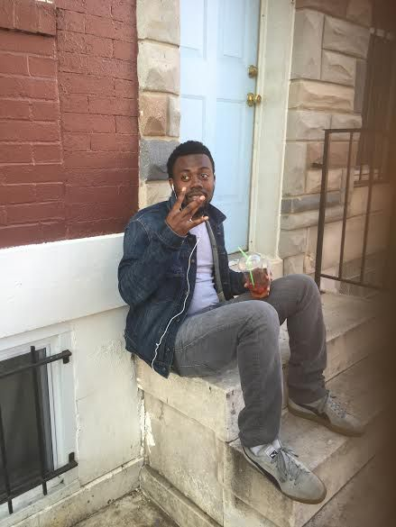 27-year-old William Stewart sits outside his West Baltimore home