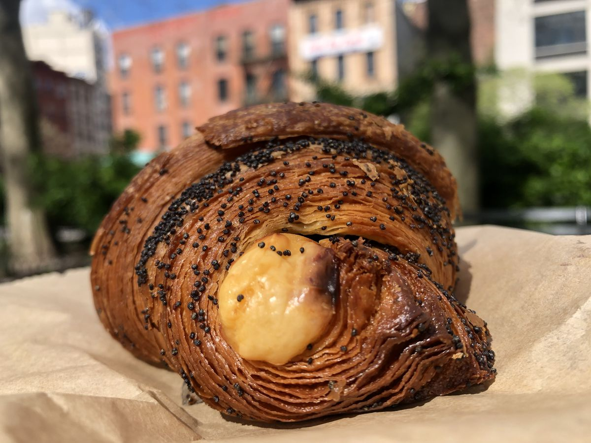 A close-up photo of a croissant filled with cheese set on a brown paper bag, with greenery in the background