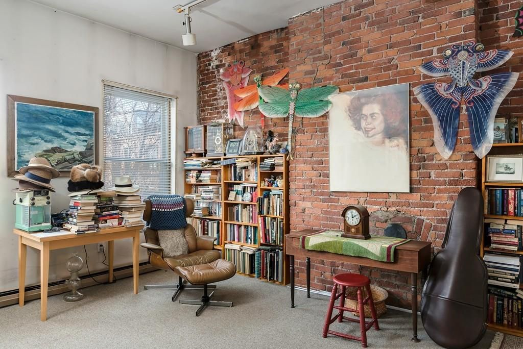 A room with a large painting of a woman on the one brick wall, and then stacks of other materials throughout.