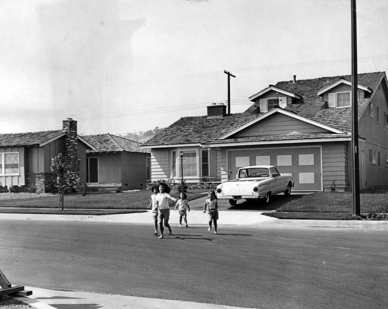 A close-up of two modest homes, both with wood siding and wood roofs, fronted by grassy yards. A car is parked in the driveway. Four children run across the street.