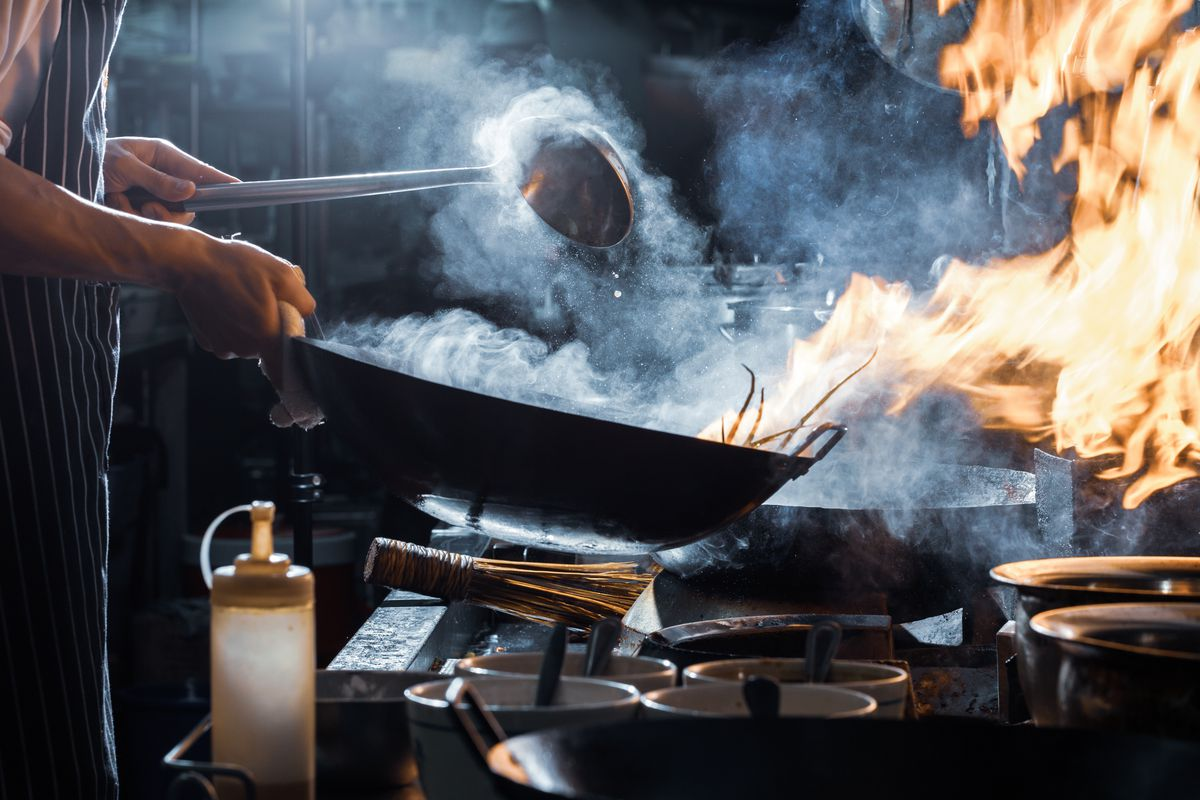 Stock photograph of a chef (bottom half visible) cooking with a fiery wok in a restaurant kitchen