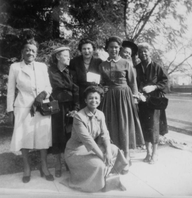 A black and white image of seven women of various ages posing for a photograph in a driveway with trees in the background. The women are finely dressed, wearing blazers, dresses and skirts, and hats.