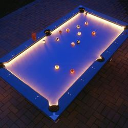 """Now you can play pool outside! It's $1 for <a href=""""http://www.opulentitems.com/Illuminated-Weatherproof-Pool-Table_p_1648.html"""" rel=""""nofollow"""">the pool table</a> and $2,999 for all the cool LED lights."""