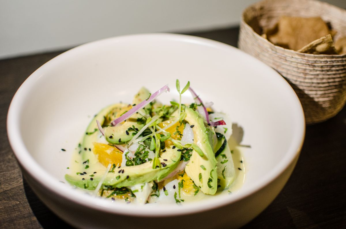 Avocado, raw fish, citrus slices, and red onions sit in a white bowl, with a basket of tostadas to the side