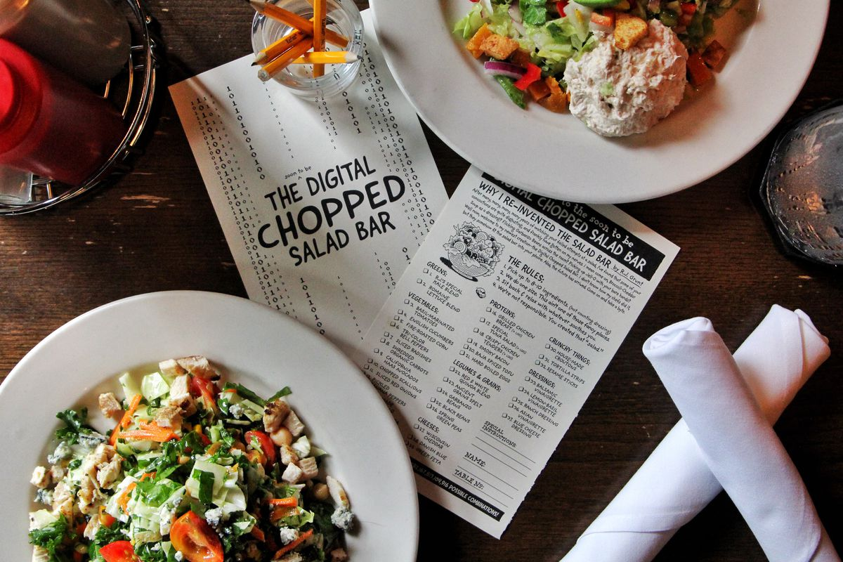 """A card that reads """"the digital chopped salad bar"""" on a wooden table between two large salads."""