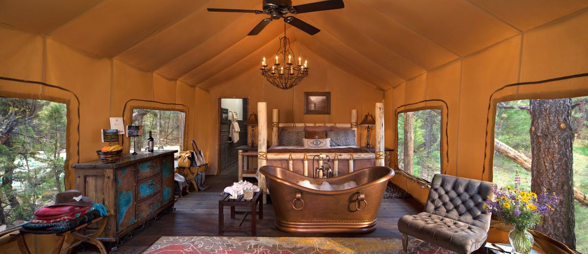 The interior of a large glamping tent at the Resort at Paws Up. There is a copper soaking tub, chairs, a dresser, a bed, an area rug, a ceiling fan, and windows in the walls of the tent.