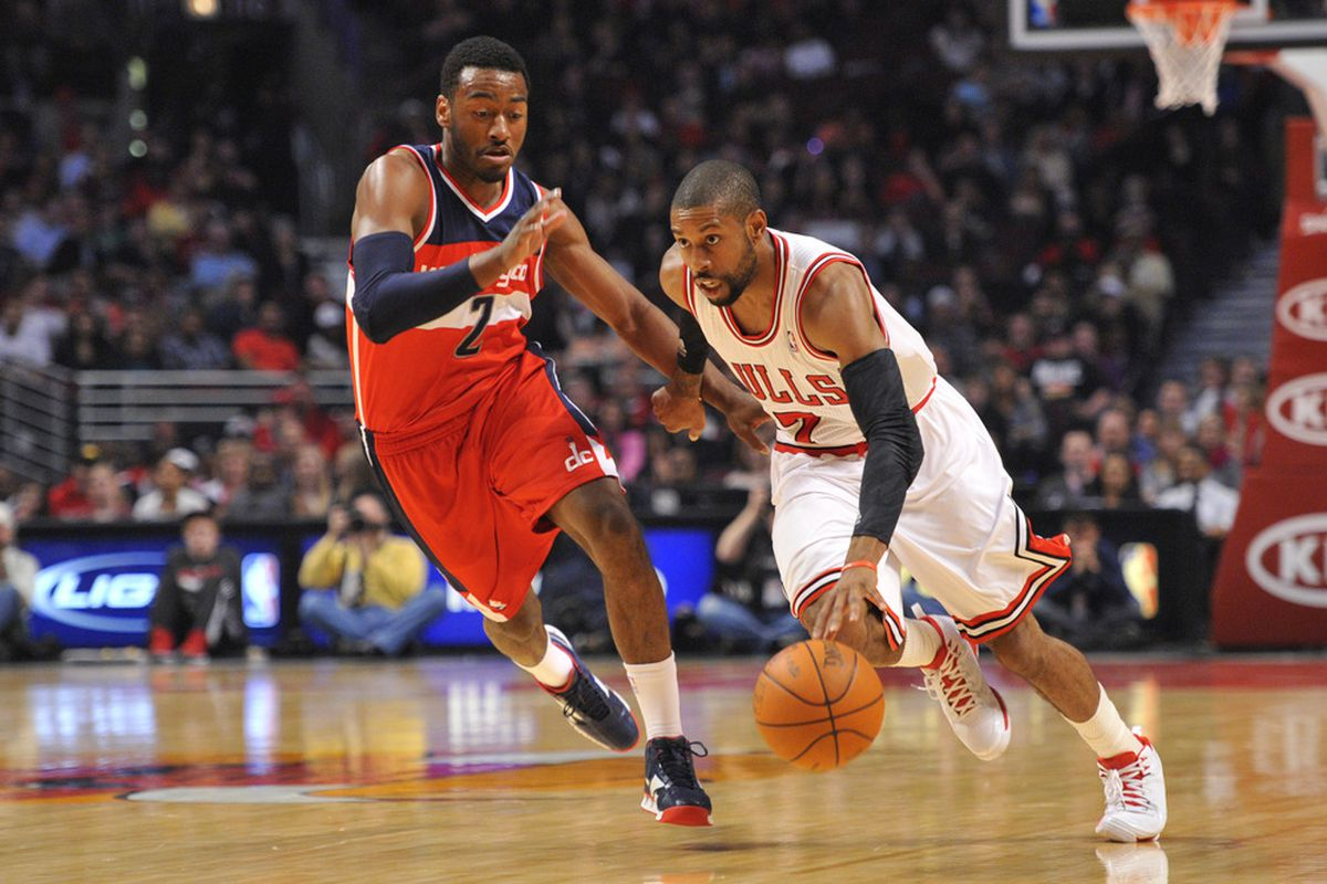 April 16, 2012; Chicago, IL, USA; Chicago Bulls point guard C.J. Watson (7) drives past Washington Wizards point guard John Wall (2) during the first quarter at the United Center.  Mandatory Credit: Rob Grabowski-US PRESSWIRE