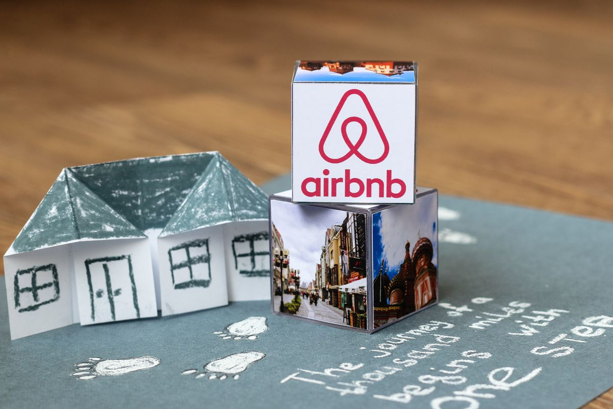 An origami house with the Airbnb logo on it.