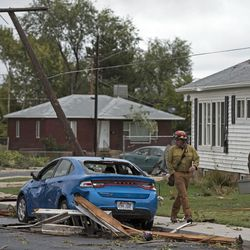 A fire official passes by a heavily damaged car after a tornado struck Washington Terrace on Thursday, Sept. 22, 2016. Officials said nobody was injured in the twister.