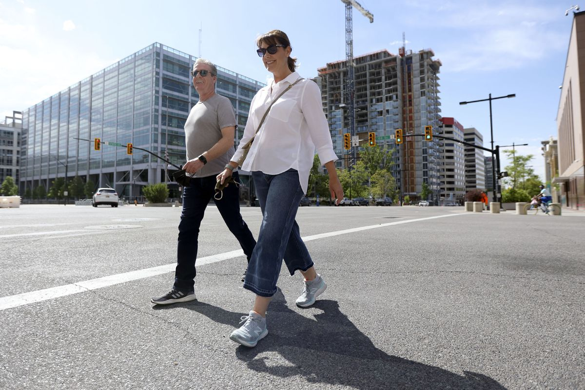 Roy and Melissa Kaiser hold their masks in their hands as they walk on State Street in downtown Salt Lake City on Friday, May 14, 2021.