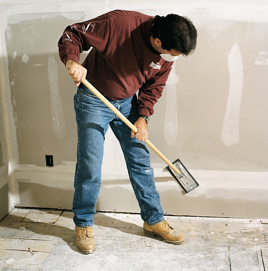 Man Sands First Coat Of Compound On Drywall With Pole Sander